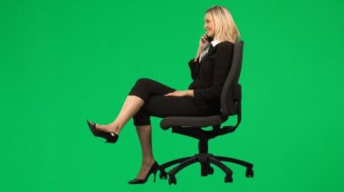 Businesswoman sitting on a chair on phone against green screen footage — Stock Video