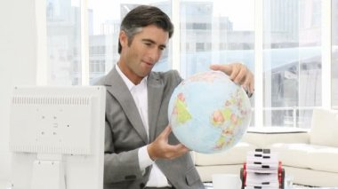 Confident businessman looking at a terrestrial globe — Stockvideo