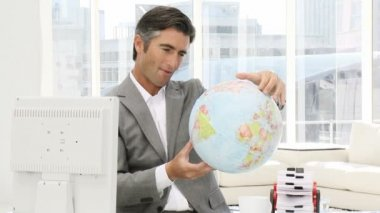 Confident businessman looking at a terrestrial globe — Stok video