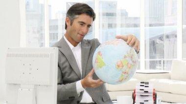 Vertrouwen zakenman kijken naar een terrestrische globe — Stockvideo