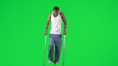 Ethnic young man walking with crutches footage — Stock Video