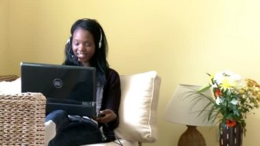Smiling woman using a laptop with headset on — Stock Video