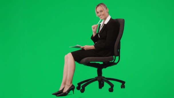 Femme assise sur une chaise, écrire des notes sur écran vert — Vidéo