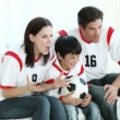 Family in Living Room watching Sport on TV - Stock Photo