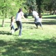 Stock Video: Parents and children playing in a park with a ball
