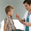 Child taking cough medicine in medical office - Photo