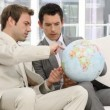 Royalty-Free Stock Vector Image: Businessmen looking at a terrestrial globe