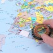 Hand moving a compass over a world map — Видео