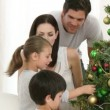 Brother and sister decorating a Christmas tree with their parents — Stock Video #15389403