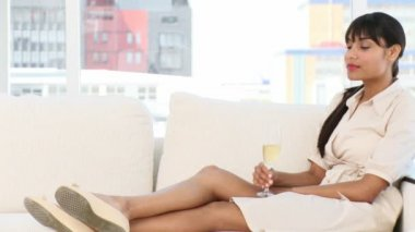 Relaxed businesswoman drinking Champagne sitting on a sofa — Stock Video
