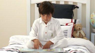 Barn läser en bok på sängen — Stockvideo