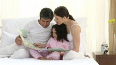 Rodzice czytanie książki na łóżku z ich córka — Wideo stockowe