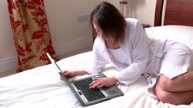 Calm woman using a laptop sitting on bed — Stock Video