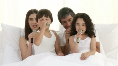 Family singing in bed with microphones — Stock Video