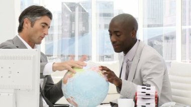 Serious businessmen looking at a terrestrial globe — 图库视频影像