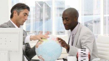 Ernstige ondernemers op zoek naar een terrestrische globe — Stockvideo