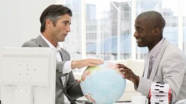 Businessmen looking at a terrestrial globe — Stockvideo