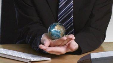 Zakenman met een roterende terrestrische globe in zijn hand — Stockvideo