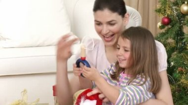Close-up of mother and daughter having fun with Christmas presents — Stock Video #15386431