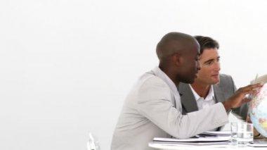 Multi-etnische zaken kijken naar een terrestrische globe — Stockvideo