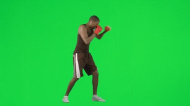 Young ethnic man boxing against green screen footage — Stock Video