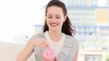 Smiling business woman inserting coin in a piggybank — Stock Video