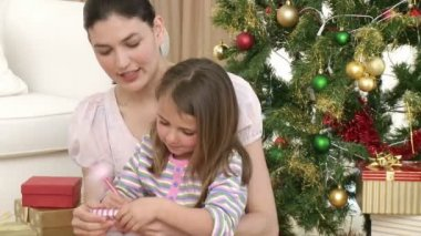 Close-up of woman and little girl playing with Christmas presents — Stock Video #15387955