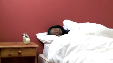 Afro-American woman in her bed looking at the alarm clock — Stock Video