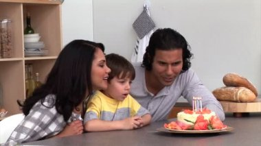 Laughing child celebrating his birthday with his parents — Stock Video #15389165