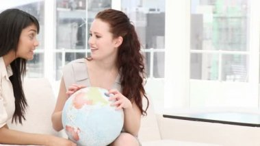 Businesswomen looking at a terrestrial globe — Vídeo de Stock