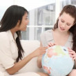 Concentrated businesswomen looking at a terrestrial globe  — Stock Video