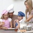 Family baking biscuits in the kitchen - Stock Photo