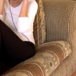 Stock Video: Attractive womlistening music sitting on sofa