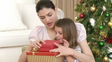 Close-up of mother and daughter opening Christmas gifts — Stock Video #15391327