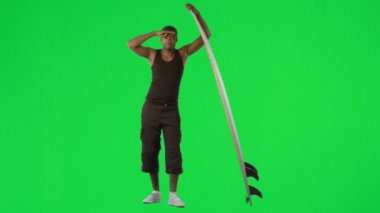 Ethnic boy with a surfboard against green screen — Vidéo