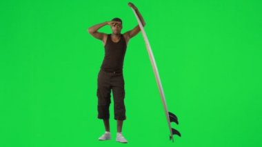Ethnic boy with a surfboard against green screen — Stock Video
