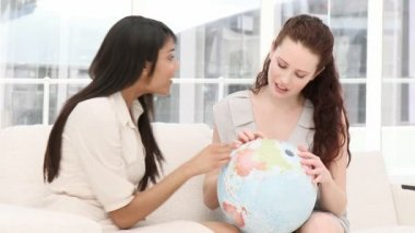 Concentrated businesswomen looking at a terrestrial globe — Стоковое видео