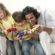 Family playing video games on the sofa — Stock Video #15404045