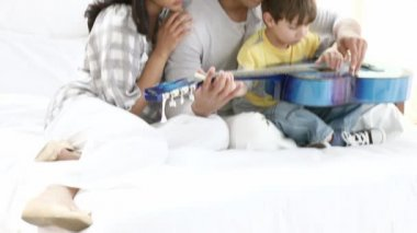 Footage in high definition of young parents and little son playing guitar on the sofa at home