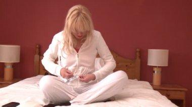 Blond kobieta pomiaru jej obwód pasa, siedząc na łóżku — Wideo stockowe