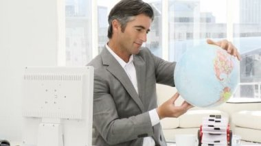 Elegant business man holding a terrestrial globe — Stock Video