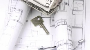 Close-up of plans, dollar house and keys turning — Stock Video