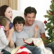 Young family having fun with Christmas gifts on a sofa at home. — Stock Video