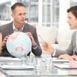 Stock Video: Manager holding a terrestrial globe in a meeting