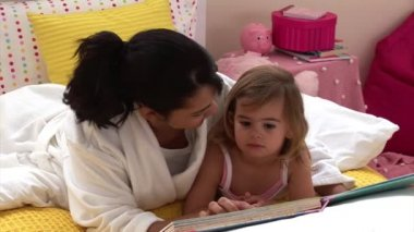Pretty woman reading a book with her daughter — Stock Video