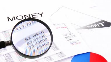Close-up of a magnifying glass showing business profits — Stock video