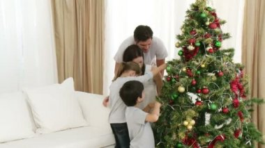 Parents and children decorating a Christmas tree — Stock Video