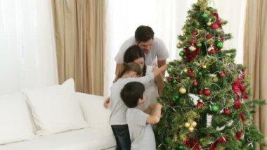 Föräldrar och barn dekorera en julgran — Stockvideo
