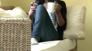 Ethnic woman sending a text message sitting on sofa — Stock Video