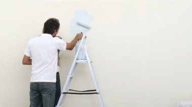 Footage in high definition of attractive couple painting a room in new house